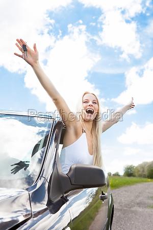 frau erhoeht hand aus autofenster
