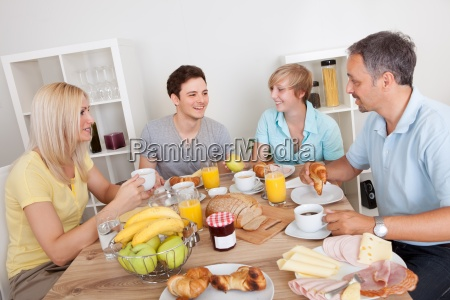 glueckliche familie geniessen fruehstueck