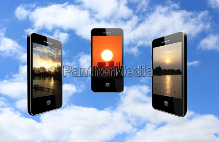 three mobile phones with different sunsets