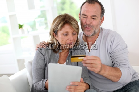 senior couple using credit card to