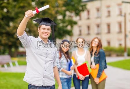 laechelnder teenager in eckkappe mit diplom