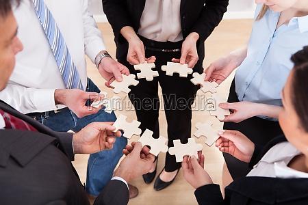 geschaeftsleute die jigsaw puzzle halten