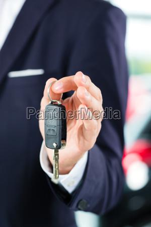 verkaeufer mit auto im autohaus