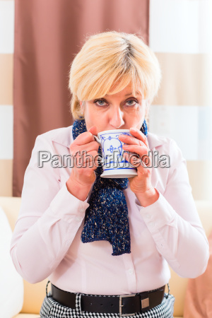senior woman drinking tea and curing