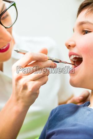 zahnaerztin behandelt junge in zahnarztpraxis