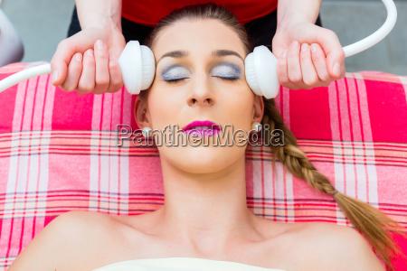 woman gets facial treatment at spa