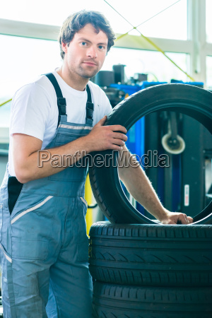 mechanic at changing tires in garage