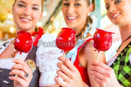 freundinnen essen kandierte AEpfel beim oktoberfest