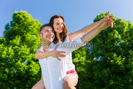 man carrying woman piggyback in the
