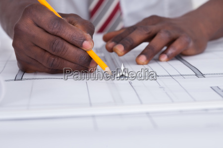 person drawing blueprint
