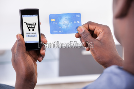 person holding credit card and mobile