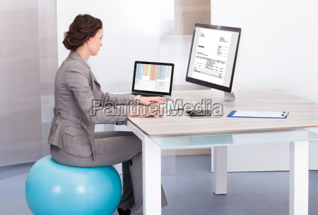 woman sitting on pilates ball using