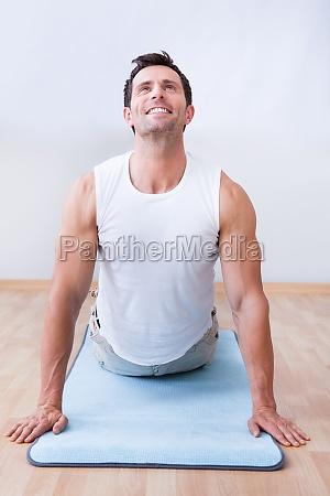 junger mann ausuebung auf gymnastikmatte