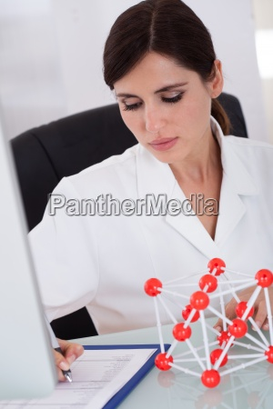 female scientist writing on notepad