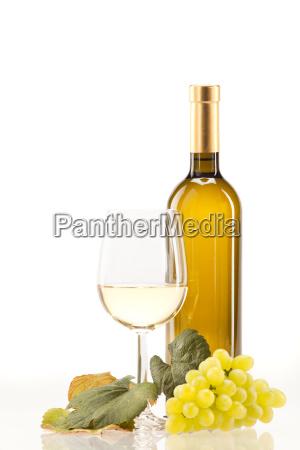 weisswein im glas mit trauben vor