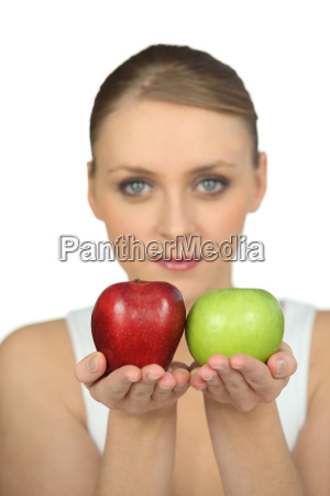 blurry woman showing apples on white