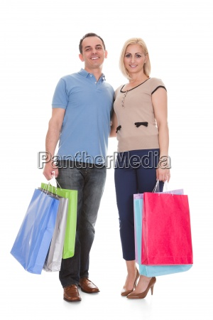 portrait of young couple holding shopping