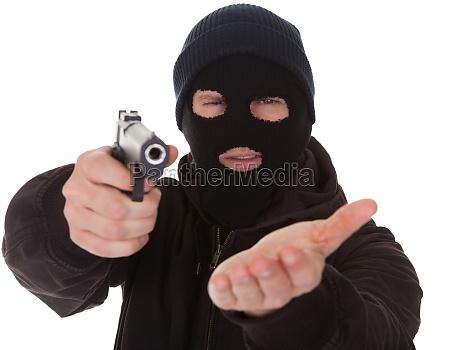 einbrecher traegt maske holding gewehr