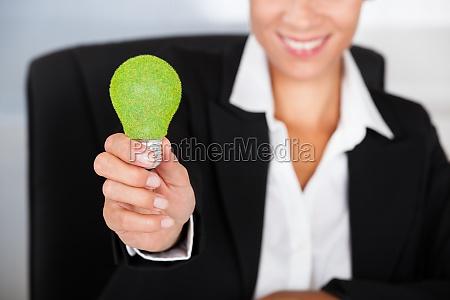 geschaeftsfrau mit gruener bulb