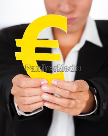 hand holding yellow euro sign in