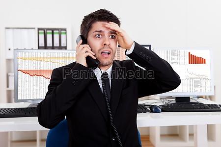 besorgt boersenmakler am telefon