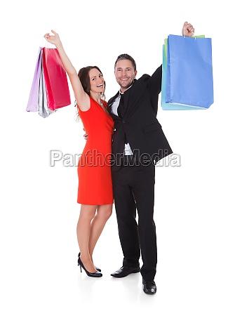 glueckliche junge paar holding einkaufen beutel