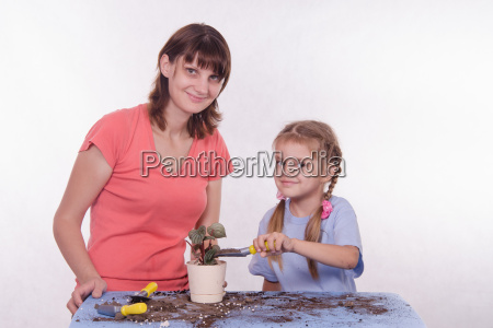daughter pours ground in a pot