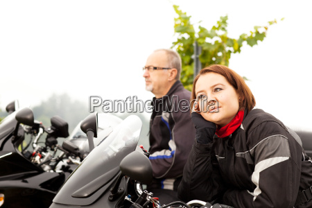 two motorcyclists take a break