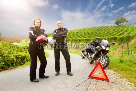 zwei motorradfahrer mit panne stehen wartend