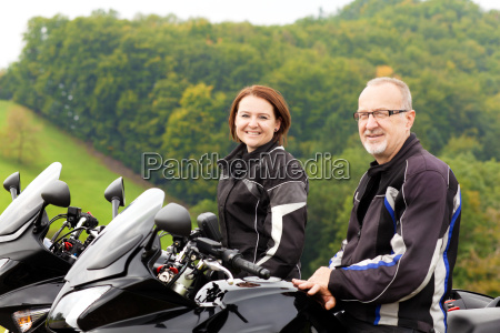 two motorcyclists sitting happy on the
