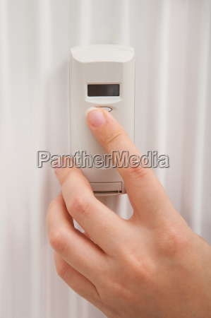 persons hand using digital thermostat