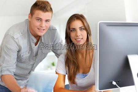 auszubildende im buero arbeiten auf desktop