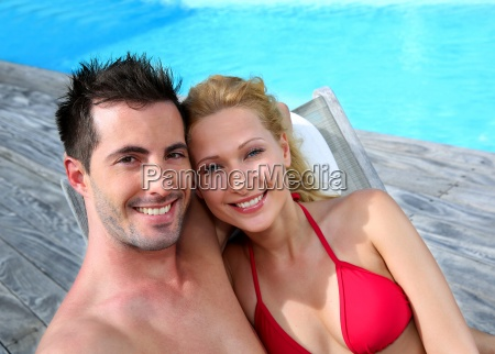 couple relaxing in long chairs by