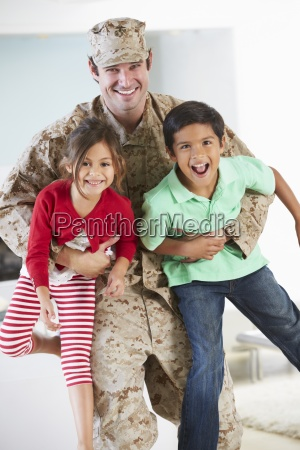children greeting military father home on