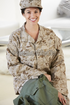 female soldier with kit bag home
