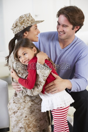 family greeting military mother home on