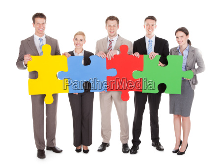 confident business people holding colorful jigsaw