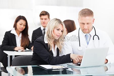 maennlicher doktor and businesswoman mit laptop