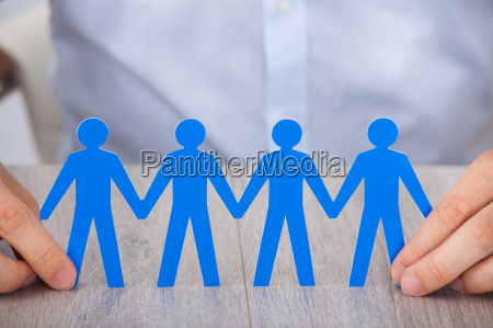 businessmans hand holding paper people chain