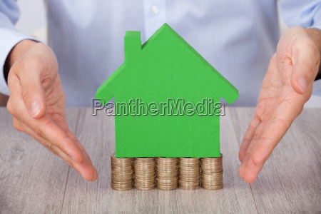 businessman presenting green model house on