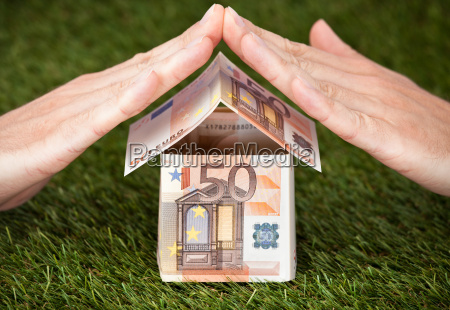 businessmans hands protecting euro house on