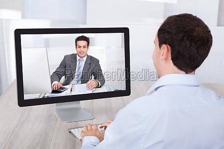 geschaeftsmann video conferencing mit mitarbeiter auf