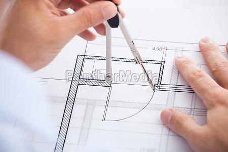 male architect using divider on blueprint
