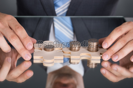 hands connecting puzzle pices with coins