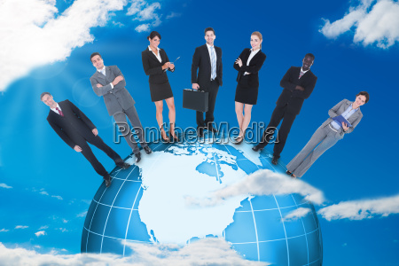 confident business people standing on globe