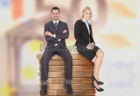 business people sitting on stacked coins