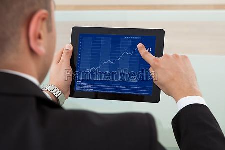 geschaeftsmann prueft den aktienmarkt am digitalen