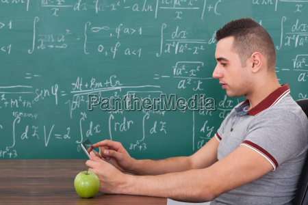 male student using digital tablet in