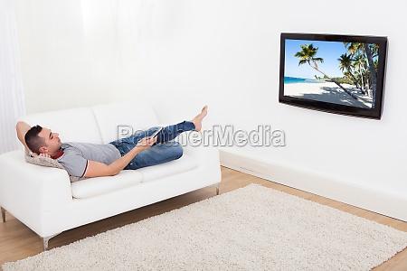 man schaut fernsehen zu hause