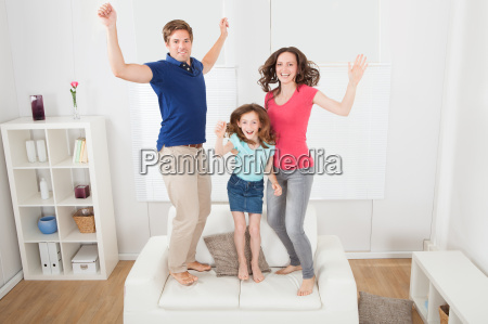 portrait of excited family jumping on